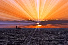 Sailboat Sunset Journey. With a silhouetted boat and and passengers taking a sailing journey with a background of clouds and the sun setting on the calm blue Stock Photo