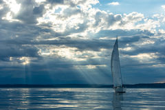 Sailboat a Sunset. Magic rays penetrate clouds at sunset behind sailboat Royalty Free Stock Photo
