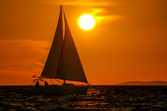 Sailboat-sunset-orange sky. Sailboat at sea close-up, sunset, orange sky, big sun