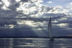 Sailboat a Sunset on Puget Sound, Washington. Magic rays penetrate clouds at sunset behind sailboat Stock Image
