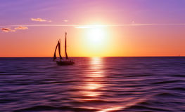 Sailboat at sunset. Sailboat silhouette at sunset in tones of purple and orange royalty free stock images
