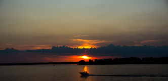 Sailboat at sunset of the Volga River. Red sunset on the river Royalty Free Stock Image