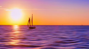Sailboat at sunset. Sailboat on waters turned purple from sunset over horizon royalty free stock photo
