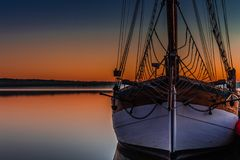 Sailboat at sunset. Sailboat on waters under orange skies at sunset or sunrise royalty free stock photos