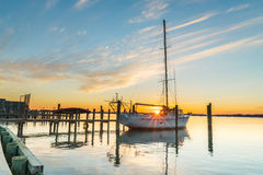 Sailboat and Sunset. The winter sun sets behind a moored sailboat on Isle of Wight Bay, Ocean City Maryland stock photo