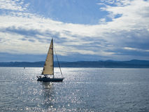 Sailboat in a sunshine. Sailboat sailing in the water reflecting sunlight Stock Photos