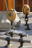 Sailboat tools. Detail of a deck on a wooden sailboat with bitts and blocks stock photos