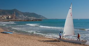 Sailboat on the coast. Sailboat with the town of Sitges in the background Royalty Free Stock Photo