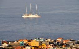 Sailboat traverses the ocean under the city of Sao Filipe Stock Photo