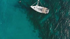 Sailboat on the turquoise sea water. Nearby vacationers swim. Aerial drone shot.  stock video footage