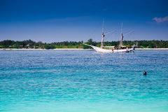 Sailboat at a turquoise tropic island Royalty Free Stock Images