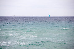 A sailboat and two seagulls in the waters of Lloret de Mar. Lloret de Mar has excellent sandy beaches grainy Stock Photography