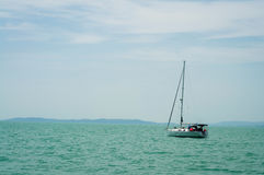 A sailboat is waiting in day stillness under beautiful blue sky with clouds on Lake Balaton, Hungary. Mountains on background. Yac. Yachting, luxury, sailing Royalty Free Stock Image
