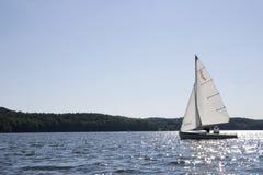 Sailboat on water. White sailboat sailing along water Royalty Free Stock Photography