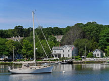 Sailboat and waterfront houses. In New England Stock Photography