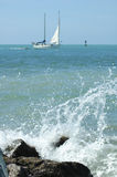 Sailboat and waves. Waves splashing in the foreground and a sailboat in the background Stock Image