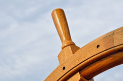 Sailboat Wheel. Wooden steering wheel of sailboat against the blue sky Royalty Free Stock Photo
