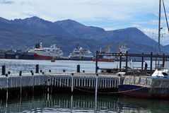 Sailboat at a wooden pier in Ushuaia Harbor with the commercial pier in the background. Sailboat at a wooden pier in Ushuaia Harbor, with ships at the commercial Stock Image