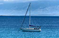 Sailboat yacht is moored in the sea bay. A ship on the ocean in Croatia with Velebit mountains in the background Royalty Free Stock Photography