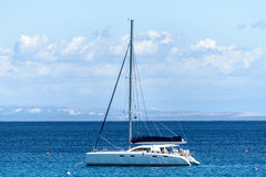 Sailboat yacht is moored in the sea bay. Stock Photos