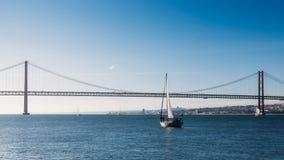Sailboats με τα άσπρα πανιά στον ποταμό Tagus, 25 της γέφυρας Απριλίου, Λισσαβώνα, Πορτογαλία στοκ φωτογραφία