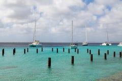 Sailboats που δένονται πέρα από το νερό και τις συσσωρεύσεις Aqua στοκ εικόνες