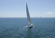 Sailboats που συναγωνίζονται στον μπλε ωκεανό ενάντια στον ουρανό Στοκ Εικόνες