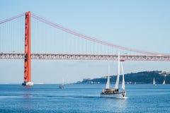 Sailboats στον ποταμό Tagus, στις 25 Απριλίου υπόβαθρο γεφυρών, Λισσαβώνα, Πορτογαλία στοκ φωτογραφία