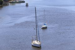 Sailboats anchored in calm blue waters at the river mouth Stock Photos