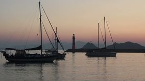 Sailboats anchored at a harbor at the Aegean coast of Turkey at dusk. Sailboats anchored at a harbor at the Aegean coast of Turkey at dusk enjoying the scenery stock video