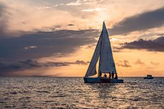 Sailboats on the background of the sunset over the sea stock image