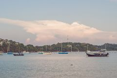Sailboats in the bay against the background of a large pink cloud royalty free stock photography