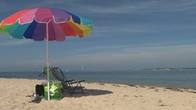 Sailboats beach chairs and umbrella scene. Video of sailboats beach chairs and umbrella scene stock video