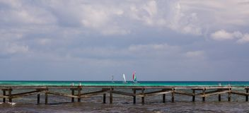 Sailboats behind Wooden Jetty in the Caribbean Stock Image