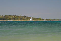 Sailboats on blue sea with seashore behind them Royalty Free Stock Images