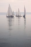 Sailboats calm water fog. Sailboats on calm water, no wind, foggy weather, dusk, reflections Stock Photo