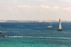 Sailboats, catamaran, and motor boat sailing in the ocean near t stock images