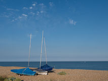 Sailboats on coast. A coast scene with sailboats pulled to the beach stock image