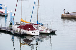 Sailboats at the dock with some people fishing. In background Royalty Free Stock Photos