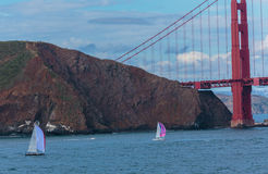 Sailboats and the Golden Gate. San Francisco, CA, USA - May 21, 2016: Two sailboats cruising near the Golden Gate Bridge in San Francisco royalty free stock image