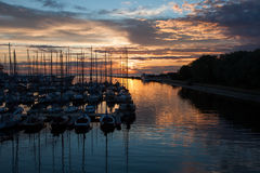 Sailboats in harbor with sunset and reflection Royalty Free Stock Images