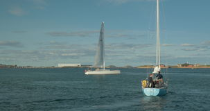 Sailboats in the harbour of Copenhagen. COPENHAGEN, DENMARK - SEPTEMBER 10, 2015: Two yachts sailing in quiet water of city harbour stock video footage
