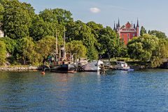 Sailboats moored on the shore of the Skeppsholmen Island Royalty Free Stock Photos