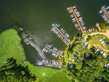 Sailboats moored to the piers. Aerial view of the lake embankment with piers and sailboats. Stock Photos