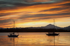 Sailboats and Mt. Baker. Sailboats anchor off of Lummi island, located in the San Juan Islands of the Puget Sound area of western Washington state. The volcano Royalty Free Stock Image