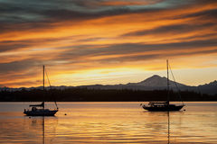 Sailboats and Mt. Baker Sunrise. Sailboats are anchored in Hales Pass in front of the active volcano Mt. Baker in the Puget Sound area of western Washington, USA Royalty Free Stock Image