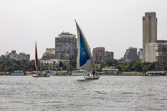 Sailboats on the Nile in Cairo in Egypt. Against the backdrop of buildings Stock Photos