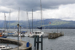 Sailboats at the port in Yvoire. Yvoire, France - May 24, 2013: Sailboats anchored along the pier at the port on Lake Geneva. Bad weather and heavy clouds caused Stock Images