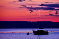 Sailboats and Red Dawn. A sailboat anchored at Lake Geneva, Switzerland silhouetted against a reddish dawn Royalty Free Stock Image