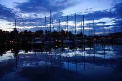 Sailboats reflecting on the water in a marina stock photos